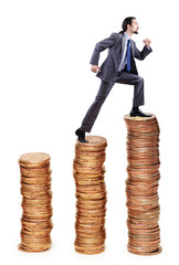 Businessman climbing gold coins stacks