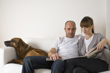 Couple sitting on sofa, looking at catalog