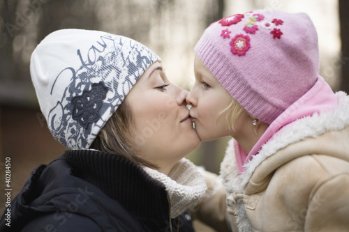 Mother kissing daughter, close-up, side view