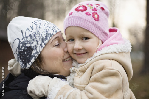 Daughter hugging mother, smiling