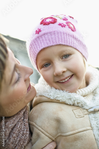 Mother smiling with daughter, close-up, portrait