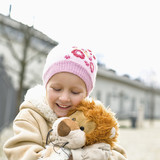 Girl holding stuffed lion, smiling