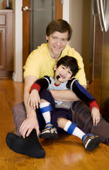 Father holding disabled son on kitchen floor