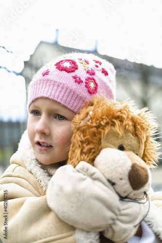 Girl holding stuffed lion, looking away
