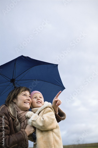 Mother with daughter holding umbrella, smiling