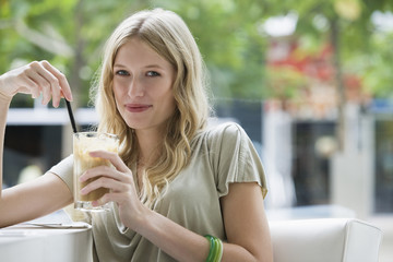 Young woman holding glass of coffee, portrait