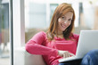 Young woman using laptop, smiling, portrait