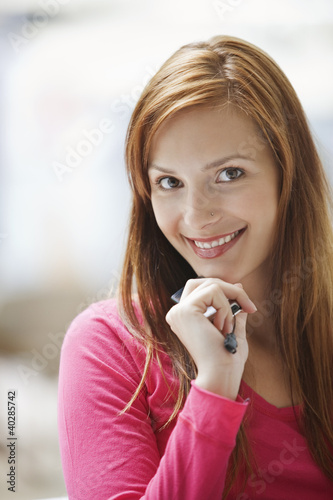 Young woman holding mobile phone, smiling, portrait