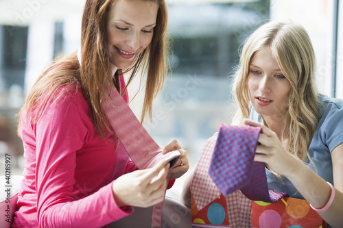 Young women looking at tie