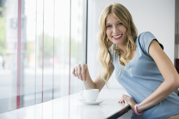 Young woman with coffee cup leaning on window sill, portrait
