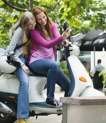Young women sitting on motor scooter while young men smiling