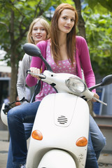 Young women sitting on motor scooter, smiling, portrait