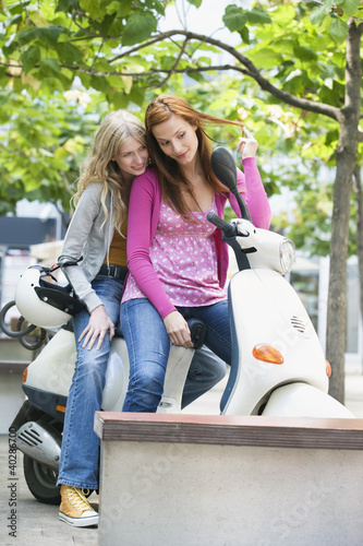 Young women sitting on motor scooter, smiling