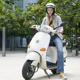 Young woman sitting on motor scooter, portrait