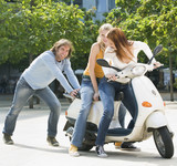 Young man pushing young women on motor scooter, smiling