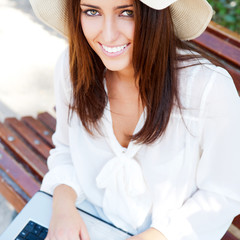 Young elegant woman wearing straw hat and white dress