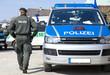 Polizist neben Einsatzwagen