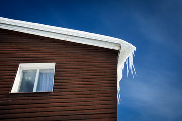 closeup of a wooden cottage roof covered with snow