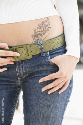 Young woman with tattoo, midsection, close-up