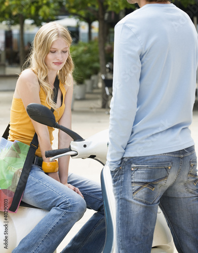 Young woman sitting on motor scooter in front of young man