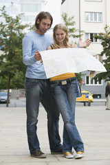 Young couple looking at map, smiling