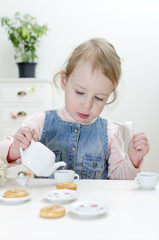 Cute little girl drinks tea with bagels