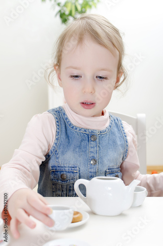 Cute little girl drinks tea with bagel