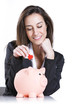 Close-up of young woman putting a red hearth  into a piggy bank,