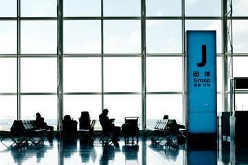 羽田空港、逆光の待合室で待つ人々