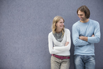 Young couple with arms crossed, smiling