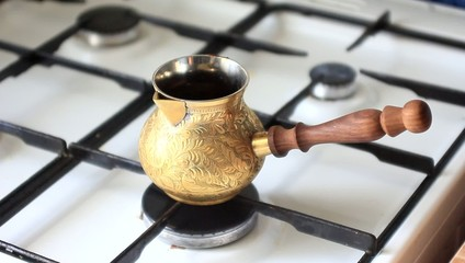 Brew coffee in brassy cezve on gas-stove