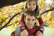 Father carrying daughter on shoulders, smiling, portrait