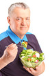 A mature man eating salad