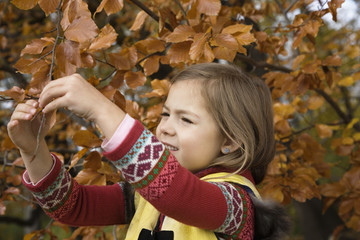 Girl holding branch of tree