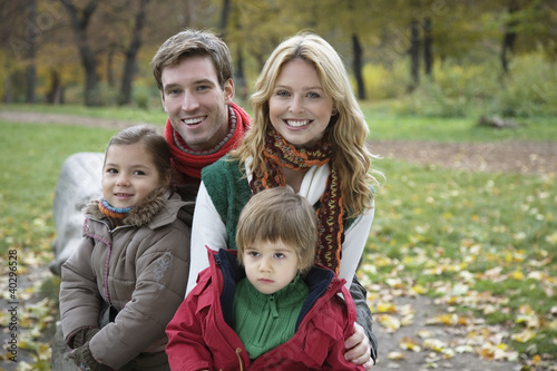 Family sitting on tree trunk, smiling, portrait