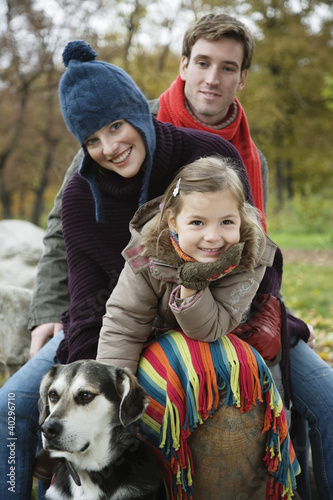 Girl sitting with parents and dog, smiling