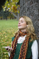 Young woman leaning by tree trunk, listening to MP3 player