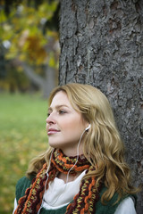 Young woman leaning by tree trunk, listening music