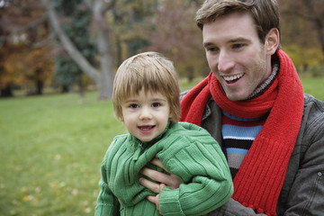 Father holding son, close-up
