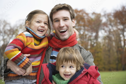 Father holding son and daughter, smiling, portrait