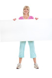 Portrait of smiling middle age woman holding blank billboard poster