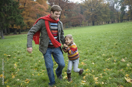 Father and daughter in garden, smiling