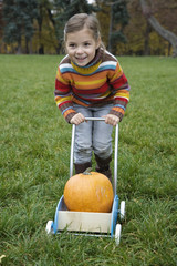 Girl pushing cart of pumpkin, smiling