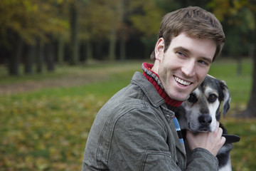 Young man with dog, smiling, portrait