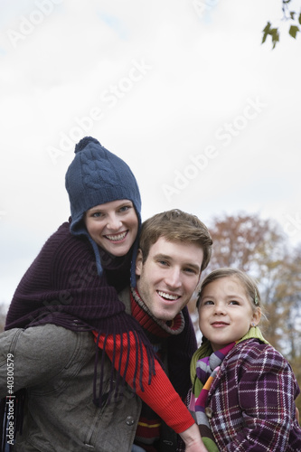 Husband giving piggyback to wife while daughter smiling