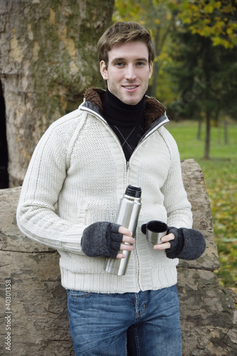 Young man holding thermos, portrait