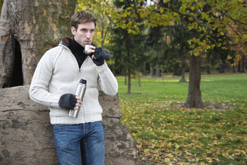 Young man holding thermos