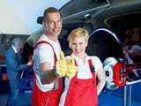 Motor mechanics and apprentice in garage show thumbs up