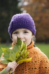 Girl holding maple leaf, smiling
