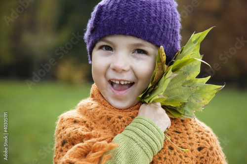 Girl holding maple leaf, smiling
